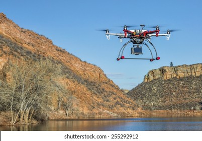 FORT COLLINS, CO, USA, February 18,  2015:  F550 Flame Wheel  hexacopter drone is  flying with a camera over mountain lake