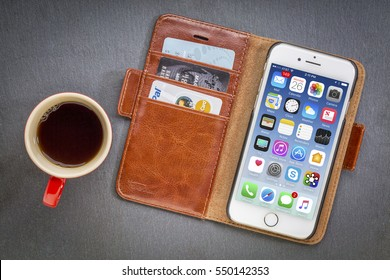 FORT COLLINS, CO, USA - JANUARY 1, 2017: iPhone 7 smart phone by Apple Computer Inc in a leather wallet with credit cards and coffee against stone background.
