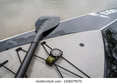 Fort Collins, CO, USA - July 22, 2019: Garmin multisport watch (Fenix 3) on a deck of stand up paddleboard used to monitor paddling workout.