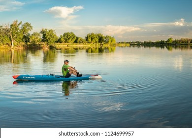 Fort Collins, CO, USA - June 22, 2018: A senior paddler resting on a racing stand up paddleboard by Starboard  after evening training workout.