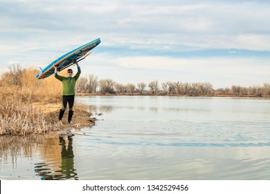 Fort Collins, CO, USA - March 12, 2019: Early spring stand up paddling, senior male launching his racing paddleboard by Starboard on a lake in Colorado