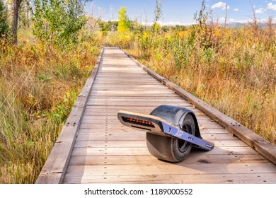 Fort Collins CO, USA - September 24, 2018:  Onewheel electric skateboard on a boardwalk across a swamp - Riverbend Ponds Natural Area.