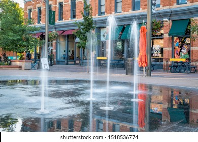 Fort Collins, CO, USA - September 22, 2019: Early morning in Old Town square with a splash pad fountain running and people sitting in a coffee shop.