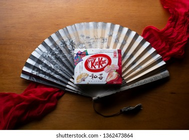 Fort Collins, CO/USA - November 26, 2018 - A Japanese Strawberry Kit Kat lies on top of a Japanese fan.