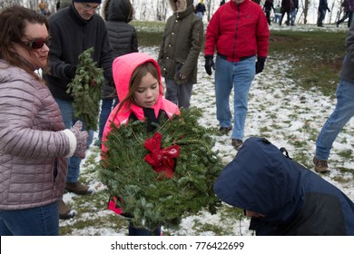 FORT INDIANTOWN GAP, PA, USA - December 16, 2017: Volunteers hand out wreaths for a grave at the National Cemetery at the Wreaths Across America event.