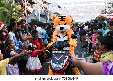 FORT KOCHI, INDIA - JANUARY 01:  Happy smiling kids competing for hand shake  with the cartoon character at a parade at carnival on Christmas and New year on January 01, 2017 Cochin, Kerala India.