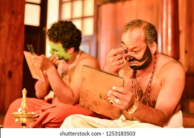 Fort Kochi, Kerala, India, 2019.Two Kathakali artists painting faces for performance. Kathakali is an Indian classical dance form which is popular in the state of Kerala performed by men.
