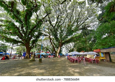 FORT KOCHI, KERALA, INDIA, OCTOBER 31, 2017: Eating out in Fort Kochi. A promenade with tables, chairs and umbrellas waiting for tourists, on a rainy day.
