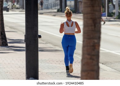 Fort Lauderdale Beach, Florida - USA - February 9, 2021: Blonde lady woman with blonde up do hair jogging and running down the paver sidewalk next to road wearing white sports top and blue yoga pants