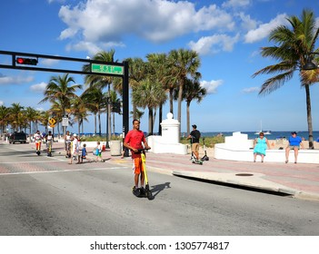 FORT LAUDERDALE, FL - FEBRUARY 3, 2019:  Man enjoys riding an e-scooter on the beach at A1A.  Fort Lauderdale is the only city in Florida that allows dockless scooters, whose riders rent via an app.