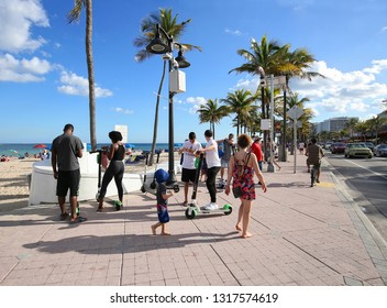 FORT LAUDERDALE, FL - FEBRUARY:  People renting e-scooters on the beach.  Fort Lauderdale is the only city in Florida that allows dockless scooters rented via an app, as seen on February 3, 2019.