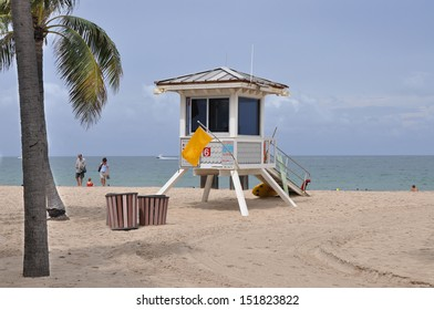 FORT LAUDERDALE, FL - JUL 18: Yellow caution flag waving outside lifeguard station on Fort Lauderdale beach which is 7 miles long, only 4 miles have public access. Fort Lauderdale Jul 18, 2013.