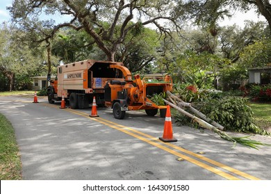 FORT LAUDERDALE, FL, USA:  Asplundh Tree Co. chipper truck loaded with palm tree trunks & branches as they clear residential electric lines to prepare for hurricane season as seen on January 28, 2020.