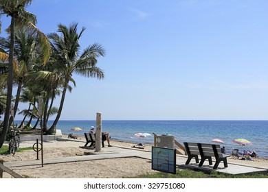 Fort Lauderdale, FL, USA - June 25, 2014: Lauderdale Beach Park Atlantic coast view being enjoyed by many people on a sunny day.  This ocean view park at the east end of 25th Street has palm trees