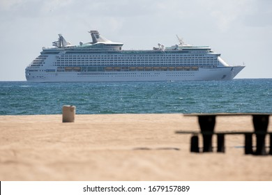 FORT LAUDERDALE, FL, USA - MARCH 21, 2020: Telephoto photo Adventure of the Seas off shore Fort Lauderdale Florida beach in foreground