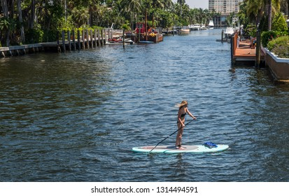 FORT LAUDERDALE, FLORIDA - JULY 14 - A woman paddleboarding along the canal on July 14 2018 in Fort Lauderdale Florida