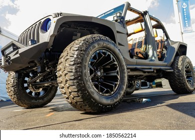 Fort Lauderdale, Florida / USA - 10/31/2020: Custom, modified, lifted and flex painted four and six wheel drive jeeps with fat off roading tires, led lights, wenches and rented rims at the boat show.