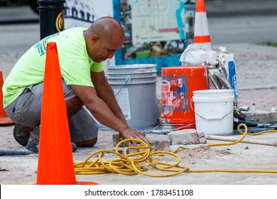 Fort Lauderdale, Florida / USA - 2/27/2019: Construction worker installing concrete red block pavers with safety cones, buckets for cement, grout and yellow electrical cables for power tools.