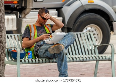 Fort Lauderdale, Florida / USA - 2/27/2019: A male construction working taking a lunch break texting his boss about the job site while eating his food in a carry out styrofoam container near his soda.