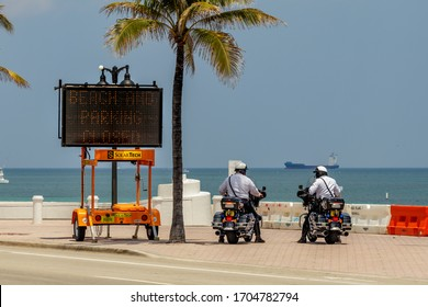 Fort Lauderdale, Florida / USA - 4/10/2020: Two Police Motor Units aka motorcycle law enforcement cops not FHP, stopped and monitoring the ocean and sand next to a Beach & Parking Closed lighted sign.