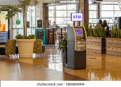 Fort Lauderdale, Florida / USA - 8/11/2020: ATM cash vending machine in front of an in mall restaurant on shiny wooden floor with large decorative planters and people near windows in background.