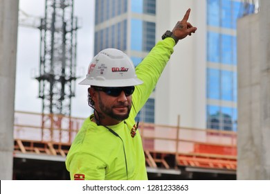 Fort Lauderdale, Florida / USA - December 20 2018: Mexican Latino construction contractor wearing hard hat, fluorescent yellow shirt, ears and safety equipment pointing in front of building and crane.