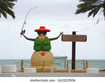 Fort Lauderdale, Florida, U.S.A - January 3, 2020 - The statue of a sandman with a hat, vest and fishing rod by the beach