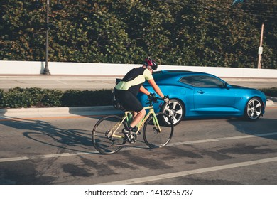 Fort Lauderdale, Florida USA - June 01, 2019: Cyclist in Yellow and Black Jacket Riding the Bike versus blue muscle car on sunrise