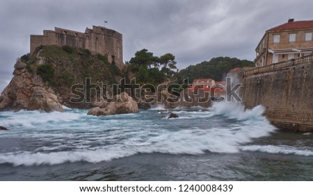 Fort Lovrijenac in Dubrovnic as seen from the beach on a stormy day, with crashing waves and dark clouds.