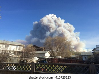 Fort Mcmurray, AB - May 1, 2016.  Residents of northern Alberta town threatened by out of control wildfire, burning 4 km west of the town. Enormous smoke clouds tower over residential areas.