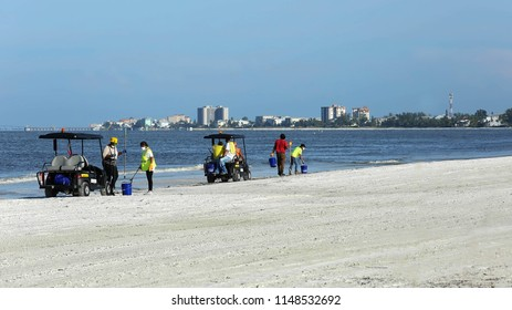 FORT MYERS BEACH, FLORIDA, USA - AUGUST:  Workers traveling the beach in golf carts and wearing surgical masks clean up dead fish that washed up due to toxic red tide as seen on August 3, 2018.