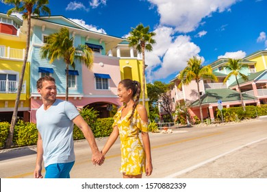 Fort Myers Beach traditional colorful cottages houses - Couple on winter vacation in sun walking holding hands near Fort Myers Beach.