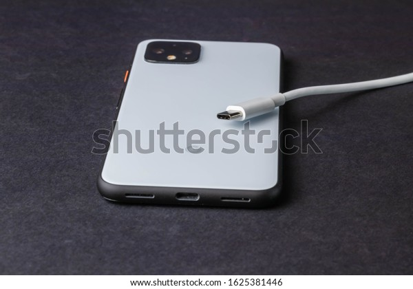 Fort Myers, Fl / USA - 1/24/20:new Pixel 4 android phone from Google in white and the USB-C charging cable isolated and shot on a studio black background close up macro shot
