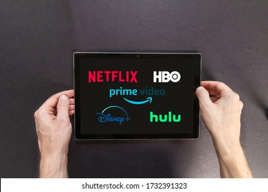 Fort Myers, Florida / USA - 5-15-20: Hands holding a tablet with major streaming logos, Netflix Hulu, amazon video, HBO, And Disney Competing video streaming subscription services. Illustrative