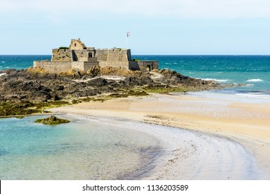 The Fort National built by french military architect Vauban on a tidal island, seen from the city of Saint-Malo, France, with the french flag blowing in the wind and a sandbank in the foreground.