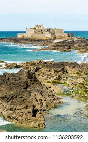 The Fort National built by french military architect Vauban on a tidal island, seen from the city of Saint-Malo, France, with the french flag blowing in the wind and rocks in the sea in the foreground