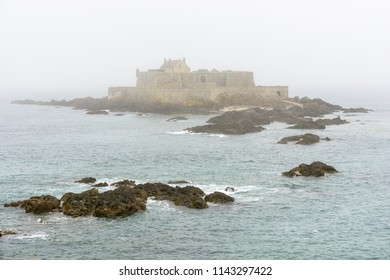 The Fort National built by french military architect Vauban on a tidal island, seen from the city of Saint-Malo, France, disappearing in the fog with rocks in the sea in the foreground.