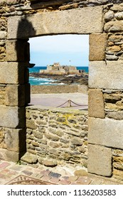 The Fort National on its tidal island, built by french military architect Vauban, with the french flag blowing in the wind seen through a stone door from the walled city of Saint-Malo in Brittany.