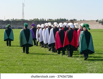 Fort Niagara, NY/USA - September 11 2005: Parade of members and volunteers of the Old Fort Niagara Association. Group of men in traditional uniforms marching towards curtain walls.