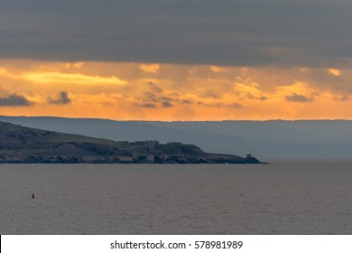 Fort on Brean Down, in front of sunset. An historic fort, last used in World War II, stands on rocks on the shore of the Bristol Channel, in Somerset, UK