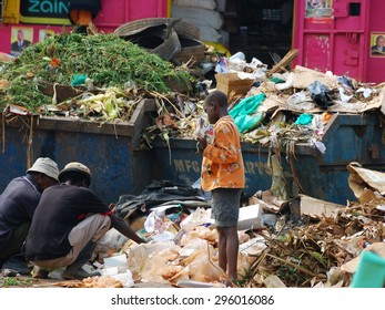 FORT PORTAL, UGANDA - AUG 28, 2010: Local people rummaging in the garbage. Nearly 40% of slum dwellers have a monthly income of just 2,500 shillings less than a dollar