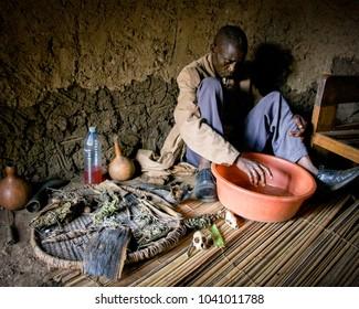 FORT PORTAL, UGANDA - Dec 2009: A Ugandan witch doctor sits among ritual paraphernalia in a small village near Fort Portal in Uganda, East Africa