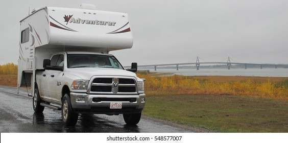 """Fort Resolution, Northwest Territories, Canada at the Yellowknife Highway. A Pickup Camper """"Adventurer"""" is mounted on a RAM 3500 Truck on road in front of the Mackenzie River Bridge in September 2014."""
