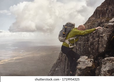 FORT WILLIAM, LOCHABER / SCOTLAND - September 13, 2019: Male climber in misty weather ascending Ledge Route, Grade 1 scramble on the North-East face of Ben Nevis mountain in Highland Scotland.