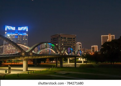 Fort Worth skyline at night with the West 7th Street bridge. Trinity park in the foreground and the downtown buildings lit up, in the background.