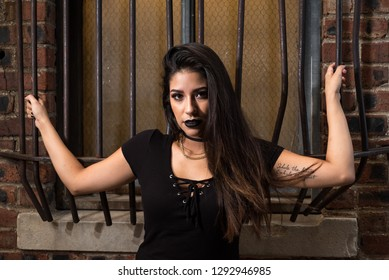 Fort Worth, Texas / USA - August 14, 2016: Portrait of a Young Hispanic Woman Wearing a Black Top and Gold Chain, Holding on to a Window Bars in a Alley