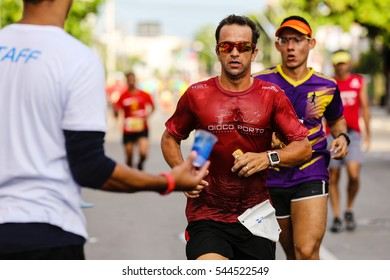 FORTALEZA, BRAZIL - JULY 10, 2016: Runner passes through an water station during the Pao de Acucar Relay Marathon Fortaleza