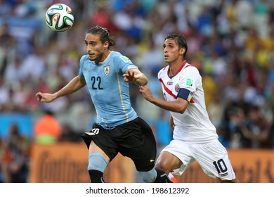 FORTALEZA, BRAZIL - June 14, 2014: Caceres of Uruguay and Ruiz of Costa Rica compete for the ball during the World Cup Group D game between Uruguay and Costa Rica at Castelao Stadium. No Use in Brazil