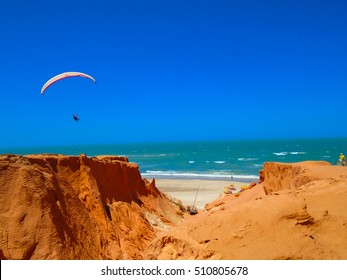 FORTALEZA, BRAZIL - OCTOBER 12, 2015: Unidentified people and paragliders at the Canoa Quebrada Beach. Gerome Bertand Saunier, Swiss pilot best known as Jeronimo, introduced this new practice