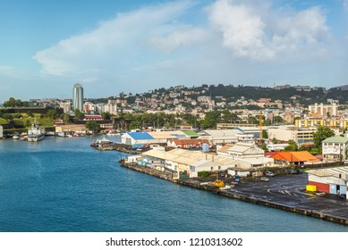 Fort-de-France, Martinique - December 19, 2016: Cityscape of Fort-de-France, Martinique, Lesser Antilles, West Indies, Caribbean. Warehouses and infrastructure of the port in the foreground.